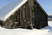 Old rustic weathered barn partially buried by snow