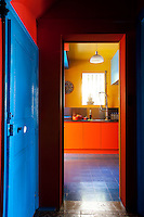 View from the hallway into the kitchen with bright yellow walls, orange units and blue tiled floor