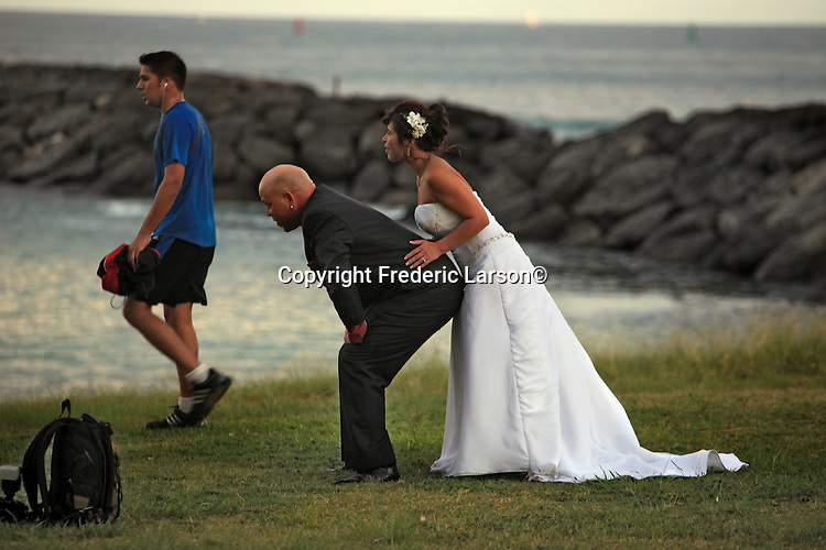 This newly wed couple appearing to be in some kind of football formation as they tried to please their wedding photographer like coming up with some creative poses on Magic Island in Hawaii. Wedding photographers realize that the wedding couple is in a state of shock taking advantage of every opportunity to put down through weird contortions to make photograph.