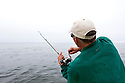 WA09892-00...WASHINGTON - Phil Russell brings in a salmon off the coast of Neah Bay. (MR #R8)