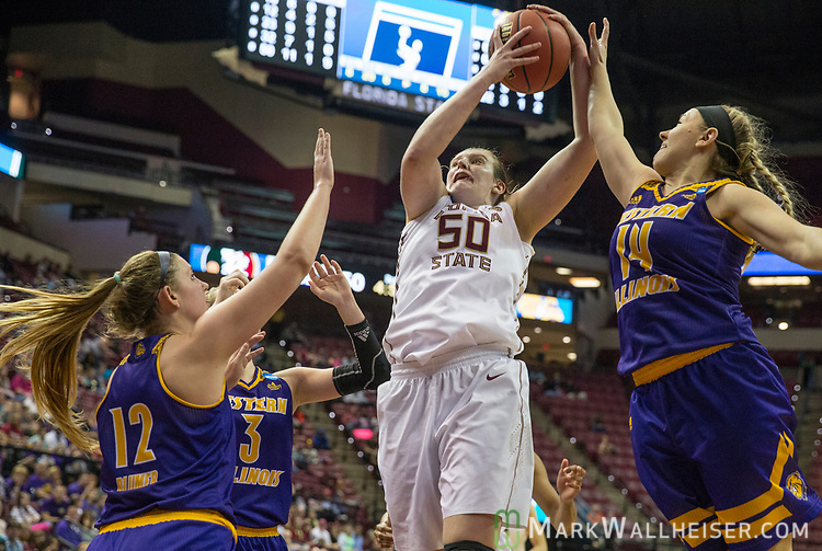 Florida State center Chatrice White comes down with a rebound over Western Illinois guard Morgan Blumer (12), Western Illinois forward Olivia Braun (3) and Western Illinois guard Taylor Hanneman (14) during the second half of a first-round game of the NCAA women's college basketball tournament in Tallahassee, Fla., Friday, March 17, 2017. Florida State defeated Westeren Illinois 87-66. (AP Photo/Mark Wallheiser)