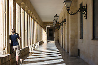 Tourist taking photograph by columns at Palace of St Michael and St George, Museum of Asian Art in Kerkyra, Corfu Town, Greece