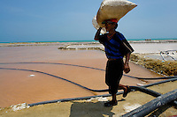 A Colombian worker carries a sack of salt in the salt mines of Salinas de Manaure, Colombia, 12 May 2007. Manaure, the arid region in northern most part of South America (Guajira Peninsula), with its very hot and dry climate throughout the year and with the naturally formed lagoons, has always been favorable for the salt production. The salt explotation, run in this area by the Wayuu Indians and later by Colombian mestizos, is known since the pre-Columbian era. Although nowadays the salt production reach to one million tons a year, processed both by industrial and artisanal methods, no social or economical development has been marked in the local community. Sea salt industry in Manaure covers the major part of Colombia's salt consumption.