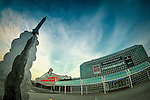 Garden City, New York, USA. December 12, 2015. Metal Rocket sculpture appears to soar into sky in front of the Cradle of Aviation Museum, with Nassau County Firefighters Museum at left. (posterization effect)