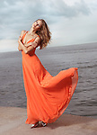 Beautiful young woman in orange summer dress flying in the wind standing on a sea shore