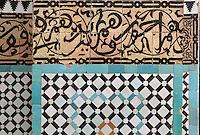 Cursive Koranic inscriptions and patterned zellige tilework from the internal courtyard of the Bou Inania Madrasa or religious school, founded in 1350 by the Marinid ruler Abu Inan Faris, Meknes, Meknes-Tafilalet, Morocco. The courtyard with its central fountain is decorated with zellige tiles in geometric patterns, carved stucco and cedar wood and is flanked by carved screens. Meknes is a fortified Imperial city redeveloped under Sultan Moulay Ismail, 1634-1727, as Morocco's political capital. Picture by Manuel Cohen