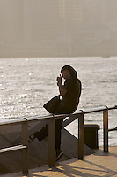 A man pauses to light a cigarette on the waterfront at Tsim Sha Tsui, in late afternoon sun. Smoking in public areas is heavily regulated, punishable by fines outside of designated areas