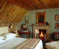 In this charming attic bedroom the fireplace has been decorated with sea shells by Sue Jones