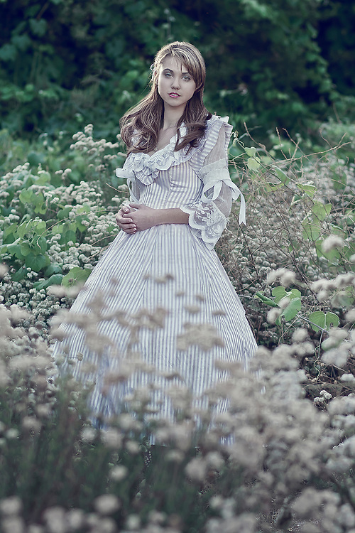 Teenage female with long hair wearing period striped long dress standing outdoors among flowers