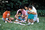 Palo Alto, CA Japanese family playing game together, children one, four and ten-years-old  MR