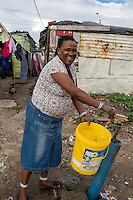South Africa, Cape Town, Guguletu Township.  Woman Getting Water at Communal Tap.