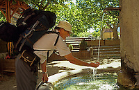 Walker drinking fresh water from village fountain. Orpiere, Hautes Alpes, France..