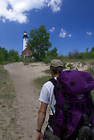 A backpacker approaches the Au Sable Point Lighthouse in Pictured Rocks National Lakeshore near Grand Marais, Mich.