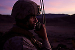 Gunnery Sgt. Arturo Blanco talks on the radio at the crack of dawn during a platoon reinforce live fire exercise at the Twentynine Palms Marine Corps Air Ground Combat Center on Friday, Nov. 30, 2012.