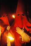 "SPA_124_xs.Hooded penitents in a night-time procession during Holy week in Seville, Spain. Street processions are organized in most Spanish towns each evening, from Palm Sunday to Easter Sunday. People carry statues of saints on floats or wooden platforms, and an atmosphere of mourning can seem quite oppressive to onlookers - In some of the processions, marchers wear clothes reminiscent of the klu klux klan but in fact their clothes are meant to depict the Nazareños, people from Nazareth. The religious fraternities and brotherhoods are responsible for carrying the statues and organizing the penitents and musicians. The Nazareños follow the people who carry the floats bearing sculptures and models of biblical scenes. The people who carry the weight of the floats are called ""costaleros"" and are expected to carry these ""thrones"" with solemnity and grace.."