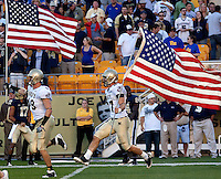 Navy players Cameron Marshall (48) and Mike Mathews (87) take the field while proudly waving the American flag. The Pittsburgh Panthers defeated the Navy Midshipmen 27-14 at Heinz Field, Pittsburgh, PA.