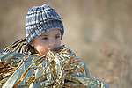 Hajem, a 2-year old Syrian refugee boy, shortly after arrival on a beach near Molyvos, on the Greek island of Lesbos, on October 30, 2015, is wrapped in insulating material in order to stay warm. He and his family were on a boat full of refugees that traveled to Lesbos from Turkey. The boat was provided by Turkish traffickers to whom the refugees paid huge sums to arrive in Greece.