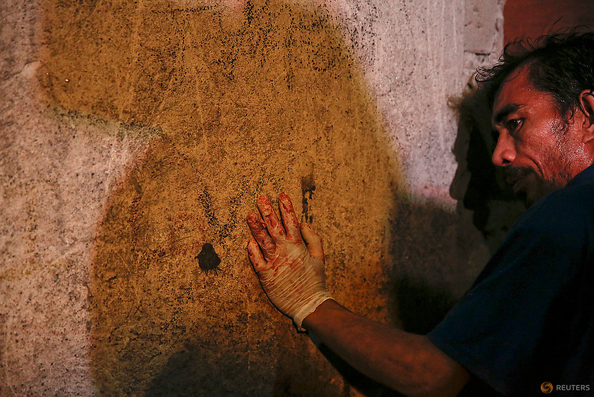 A funeral parlour worker, whose hands are bloodied from carrying bodies of killed people, rests against the wall of a house in Manila, Philippines early November 1, 2016. According to police and witnesses, unknown masked gunmen killed five people inside a house that is a known drug den. REUTERS/Damir Sagolj