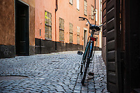 Bicycle leaning against wall on narrow cobble stone street, Gamla Stan, Stockholm, Sweden
