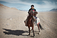 """Haji Roshan, current """"Khan"""" of the Afghan Pamir and son of the late Abdul Rashid Khan. On his way home on his horse. ..Ech Keli, Er Ali Boi's camp, one of the richest Kyrgyz in the Little Pavmir..Trekking with yak caravan through the Little Pamir where the Afghan Kyrgyz community live all year, on the borders of China, Tajikistan and Pakistan."""