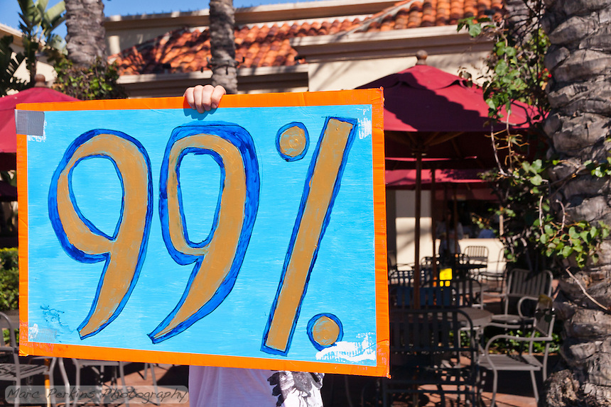 A woman (Charlie) holds a blue, red, and gold 99% sign while walking in front of an outdoor restaurant during the Occupy Orange County, Irvine march on November 5.