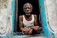 A Cuban man, the Palo Monte priest, wearing a typical red and white bracelet, looks out of the window in Havana, Cuba, August 19, 2009. The Palo religion (Las Reglas de Congo) belongs to the group of syncretic religions which developed in Cuba amongst the black slaves, originally brought from Congo during the colonial period. Palo, having its roots in spiritual concepts of the indigenous people in Africa, worships the spirits and natural powers but can often give them faces and names known from the Christian dogma. Although there have been strong religious restrictions during the decades of the Cuban Revolution, the majority of Cubans still consult their problems with practitioners of some Afro Cuban religion.