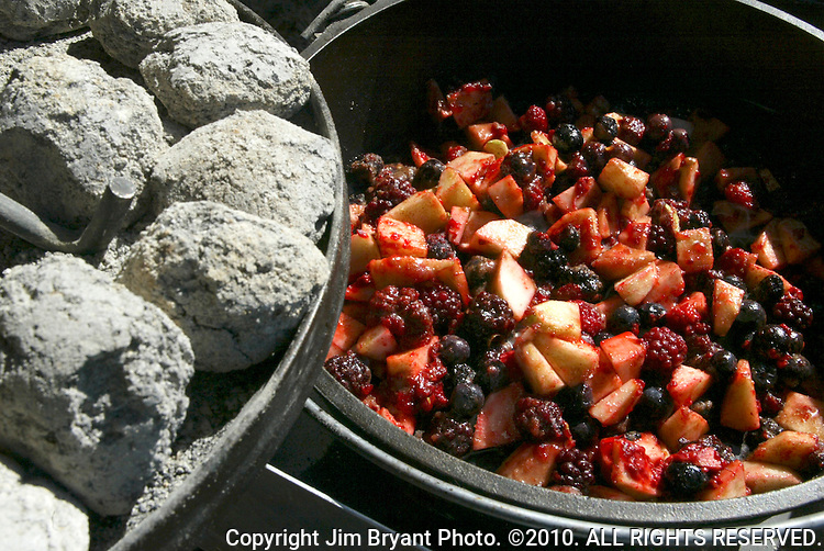 Five berry crumble cooking in Dutch oven over charcoal. Gary Butterfield and Dale Beam, members of the Puget Sound Dutch Oven Society teach classes in how to cook a variety of food and deserts in Dutch Ovens using charcoal briquettes.  Jim Bryant Photo. &copy;2010. All Rights Reserved.