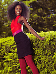 Smiling young black woman with big hair in trendy colorful clothes in a park