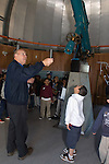 Oakland CA Older man volunteer instructing visiting second grade students on school field trip about operation of major telescope at the Chabot Space and Science Center