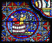 Harvest and treading of the grapes, with 2 men treading grapes in a barrel while one of them picks the grapes from the vine and collects them in a basket, section of September from the Zodiac and the labours of the months stained glass window, 1217, in the ambulatory of Chartres Cathedral, Eure-et-Loir, France. This calendar window contains scenes showing the zodiacal symbol with its corresponding monthly activity. Chartres cathedral was built 1194-1250 and is a fine example of Gothic architecture. Most of its windows date from 1205-40 although a few earlier 12th century examples are also intact. It was declared a UNESCO World Heritage Site in 1979. Picture by Manuel Cohen