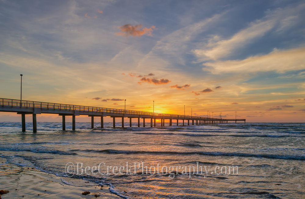 Captured this sunrise as it was coming up under the fishing pier at Port Aransas sea shore as we walked along the beach where the surf brought in some red sea weed on to the beach with the tide from the night before.