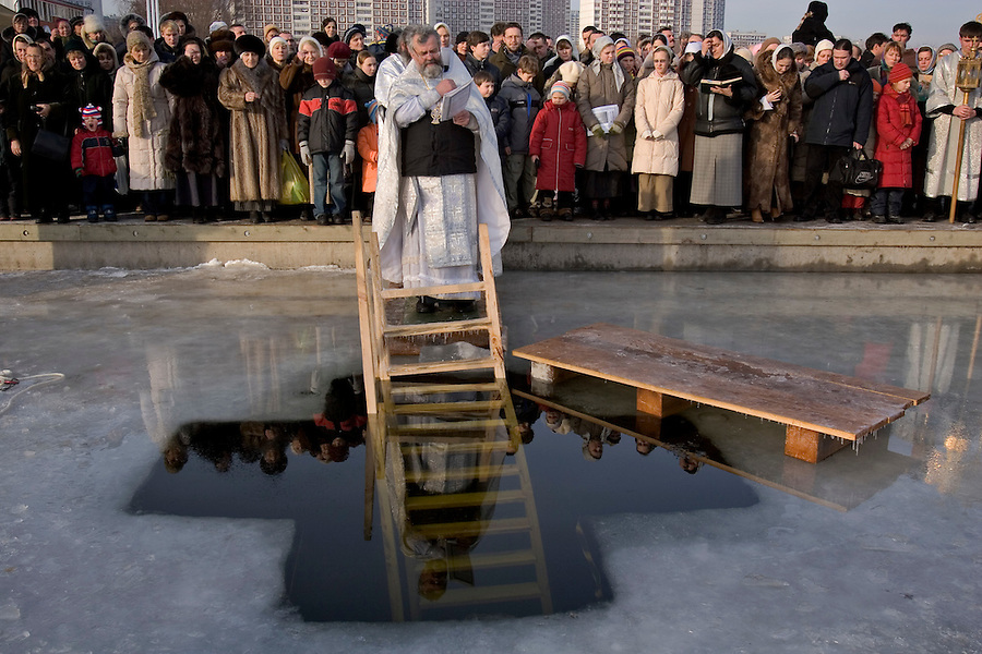 Moscow, Russia, 19/01/2005..Russian priests and Orthodox believers celebrate Epiphany at Serebryany Bor in northern Moscow. Priests blessed the waters and followers baptised themselves by total immersion in the freezing Moscow River through ice holes cut in the shape of a cross.