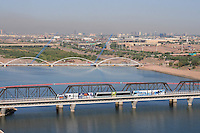 Tempe, Arizona. An aerial western view of Tempe Town Lake showing the Light Rail bridge and a light rail passing through it. The city of Phoenix skyline is seen the background. The two blue cranes next to the pedestrian bridge (white archs) are at the construction site where a new dam is being built. Photo By Eduardo Barraza © 2015