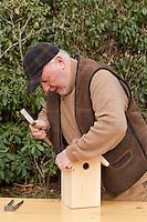 Nistkastenbau, Älterer Mann, Großvater, Opa baut einen Vogel-Nistkasten für Meisen aus Holz, fertiger Bausatz