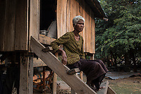"""Cambodia - Kampong Speu Province - Toun Manh, 73, sitting on the staircase of her house in Thnal village. Toun was expropriated of 1,5 hectares of land, and was compensated with just half a hectare. Given her old age, though, she cannot clear the new land for planting rice and is therefore forced to buy it on the market. The mother of 5 kids, Toun survives thanks to the support of her 15-year-old orphaned grandson. """"But if he gets sick one days, how will I manage?"""" she asks worried."""