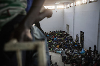 A group of sub-Saharan illegal migrants and refugees is crowded into one section of the Zawiyah detention centre, a warehouse-like facility holding as many as two thousand detainees at any one time, making it the largest of its type on Libyan soil. The centre serves as a distribution facility in the human trafficking supply chain, and from here inmates are resold to other militias on the west coast of Libya.