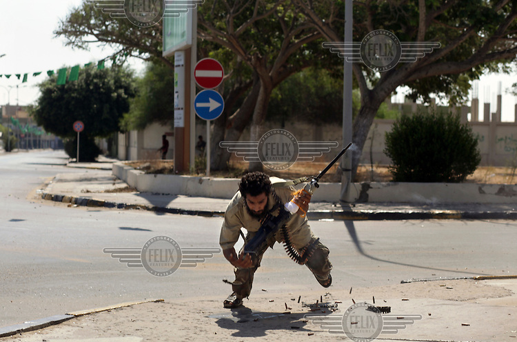A rebel fighter dives to the ground during a fierce firefight with loyalists of the Qaddafi regime in the Abu Salim district.