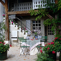 A table laid with a green and white gingham table cloth and surrounded by green chairs is set for lunch in this sheltered courtyard
