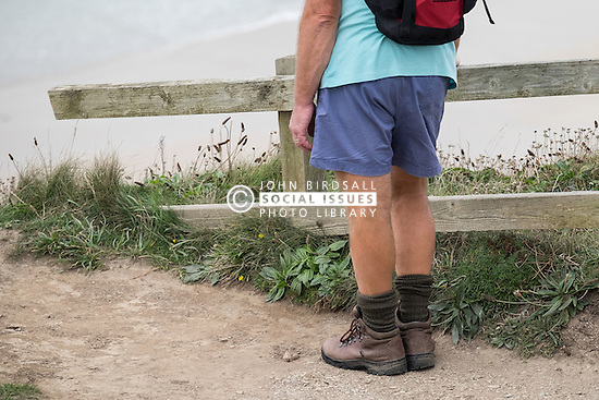 A walker takes a break on the South West Coastal Path in Cornwall.