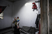 SYRIA, HOMS, Baba Amro: A Syrian woman and a child are seen in their house in Baba Amro, southern neighborhood of Homs, after Al Assad Army bombed it, on February 06, 2012.  ALESSIO ROMENZI