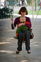 Mother and young son sitting on a swing in a city park.