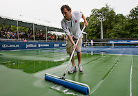 Tournament worker Sam Ross cleans off the court following a thunderstorm during the Legg Mason Tennis Classic at the William H.G. FitzGerald Tennis Center in Washington, DC.