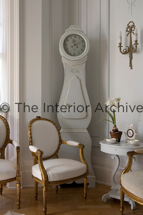 Three gilded Gustavian carver chairs and a Mora clock in a corner of the living room