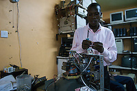 Repairing a monitor, Fortress computer store, Kampala Road, Kampala. The owner travels to China, four times a year to bring back a quater of a container-load of old computers. A typical machine might be eight years old and retail for as little as $120. Broken machines are canabalised for parts to make others work.