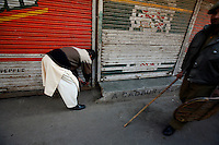 A man hurridly locks his shop as paramilitary police and  stone throwing youth clash following Friday prayer at the Jamia Masjid mosque.  Srinagar, Kashmir, India. © Fredrik Naumann/Felix Features