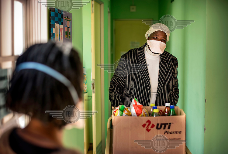Staff at a TB clinic distribute food to sick patients. Inside the clinic it is compulsory to wear a mask. The tuberculosis bacteria is transmitted carried in airborne particles, called droplet nuclei, and poor ventilation inside crowded houses is one of the main causes of infection. The clinic has a system that exchanges with the outside air.