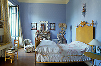 A charming girl's bedroom in a French country house where fresh blue-and-white wallpaper creates a backdrop for bedding and upholstery in pretty floral prints