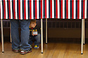 WILTON, NH - JANUARY 09: 4 year old Cameron Carbone peeks out of the voting booth as his father votes at Town Hall on January 10, 2012 in Wilton, New Hampshire. New Hampshire voters are casting ballots in the nation's first primary today.  (Photo by Matthew Cavanaugh/Getty Images)