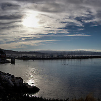 Morning sun is filtered through high clouds while fog still hugs here and there.  On a Sunday morning the harbor is filled with the masts of bearthed fishing boats and pleasure boats.  Pillar Point Harbor on the California coast.