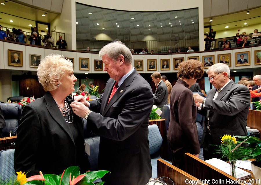TALLAHASSEE, FLA. 3/8/11-OPENINGDAY030811 CH-Sen. John Thrasher, R-St. Augustine, second from left puts a pin on the lapel of his wife Jean as Sen. Mike Bennett, R-Bradenton, right, does the same to spouse Dee during the opening day of the 2011 legislative session Tuesday at the Capitol in Tallahassee. The pins were given to the spouses by Stephanie Haridopolos, the wife of Senate President Mike Haridopolos, R-Melbourne..COLIN HACKLEY PHOTO